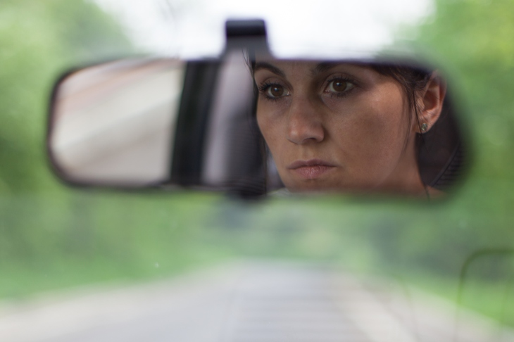 young woman reflection in rear view mirror